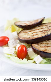 Salad with grilled eggplants, tomatoes, feta cheese and lettuce. Closeup