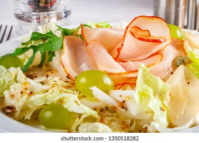 Salad with ham, iceberg, pear, grape and pumpkin seeds on white plate. Close up