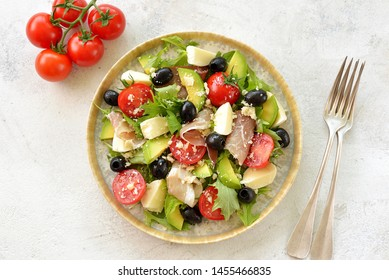 Salad with ham, mozzarella, avocado, cherry tomatoes, black olives and parmesan. Healthy food. Top view.