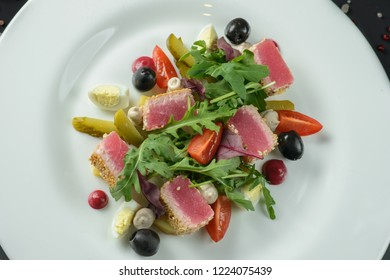 Salad with ham on white plate decorated on dark background