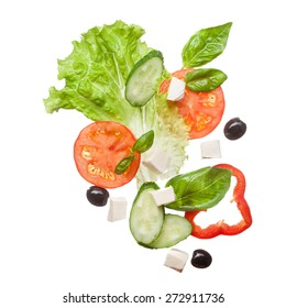 salad isolated in white - red tomatoes, pepper, cheese, basil, cucumber and olives, top view