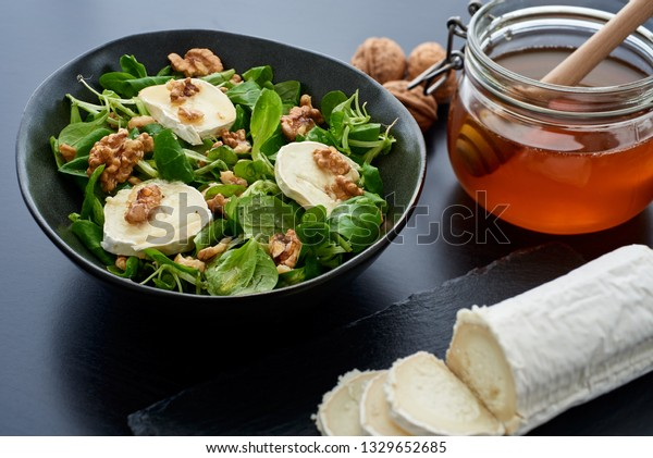 Salad of lamb's lettuce, goat cheese, walnuts, closeup, hard focus, honey stick, with big depth of field