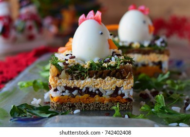 Salad in layers with chicken liver, onions, carrots, black and white rice, parsley and dill decorated with chicken head made from boiled egg