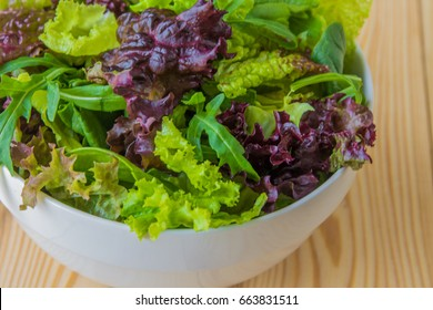 Salad leaves, purple lettuce, spinach, arugula. Mixed fresh salad in a white bowl.