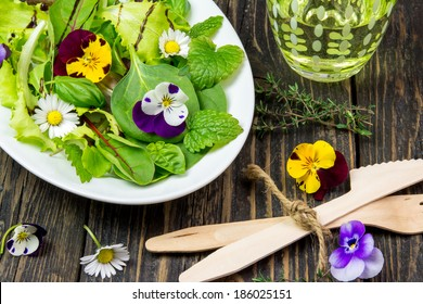 Salad leaves with wild flowers and herbs on a white plate on a vintage wooden surface, a glass of water, wooden cutlery
