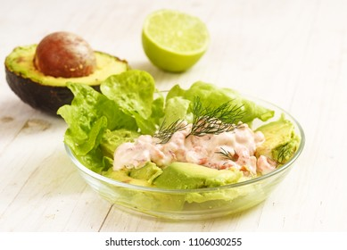 salad from lettuce, crabs in cream and avocado in a glass bowl on a white painted wooden table, selected soft  focus, narrow depth of field