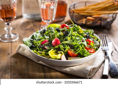 Salad with lettuce, tomato,  radish and arugula served on the plate.
