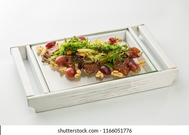 salad with meat, grapes and nuts on a plate isolated on white background.