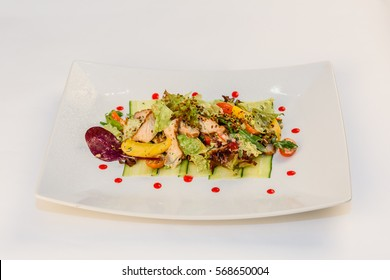 Salad with meat, vegetables and greens on a white plate