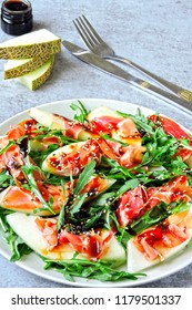 Salad melon prosciutto with arugula. Italian Cuisine. Fresh melon with prosciutto. Traditional Italian salad with arugula, melon and prosciutto.