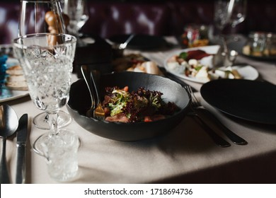 Salad on a black plate in a restaurant
