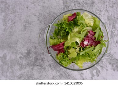 Salad. Organic food. Healthy vegetable salad with escarole endive, frisee endive, chicory radicchio, lettuce in a glass bowl. Gray table top background. Top view. Space for a text.