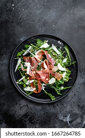 Salad with Parma, prosciutto ham, arugula and Parmesan. Black background, top view, space for text