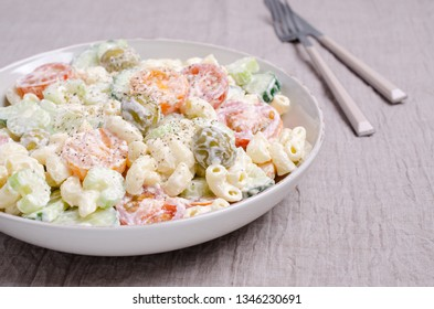 Salad with pasta and raw vegetables in a bowl on a textile background. Selective focus.