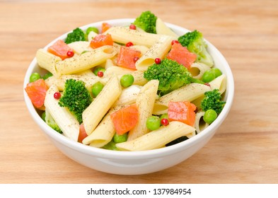 salad with pasta, smoked salmon, broccoli and green peas in a white bowl on a wooden table, horizontal top view