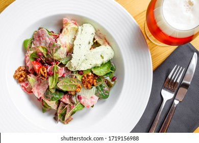 Salad with pate of cheese with spices, baby spinach, cherry tomatoes, lettuce and dressing.