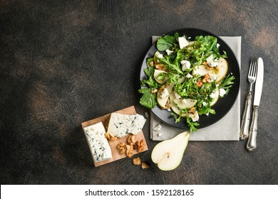 Salad of pear, blue cheese, arugula and nuts with spicy dressing on a dark background. Top view free copy space. Healthy eating.
