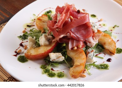 Salad with pears and meat on plate