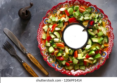 Salad with pepper avocado cucumber and yoghurt-mint sauce