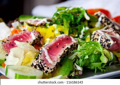 Salad with pieces of medium-rare grilled tuna