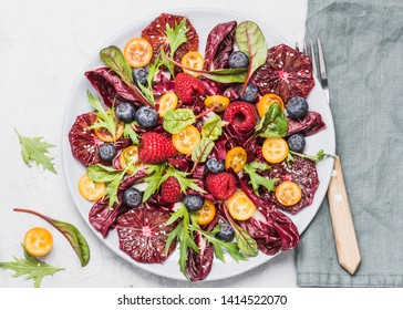Salad plate with greens, oranges and berries copy space top view. Healthy raw food concept.