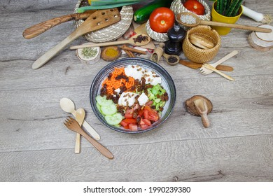 Salad plate made with carrots, radish, cucumber, tomatoes, edamame, grapes, chicken breast, served on a wooden table. Decoration in background with vegetables.