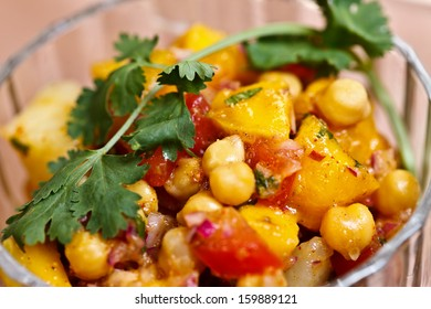 Salad of potato, chickpeas and mango??s tossed with tangy spices and fresh herbs