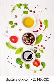 Salad preparation with dressings,olives, wild herbs leaves, chili, oil and tomatoes on white wooden background, top view
