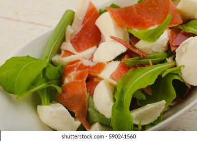 Salad with proscuitto, mozzarella, rucola and olive oil