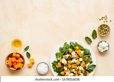 Salad with pumpkin and basil - near ingredients - on beige background top-down copy space