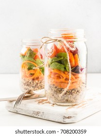 Salad with quinoa, carrots, greens and tomatoes, homemade in a jar