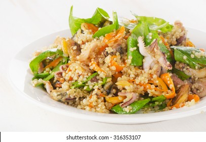Salad with quinoa and seafood on a white plate. Selective focus