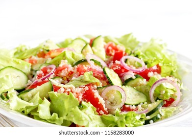 salad with quinoa. simple  vegetables - tomatoes, cucumbers, onions, lettuce and quinoa grains. Fresh vitamin salad.