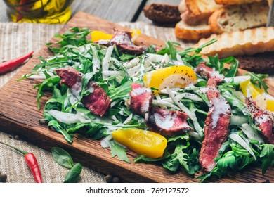 Salad with rare sliced beef, arugula, celery and peach on wood board