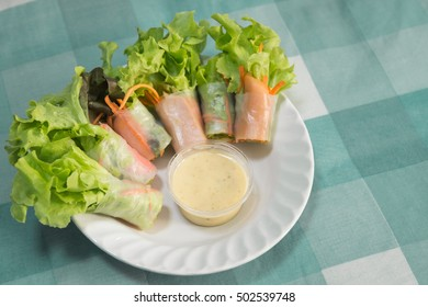 Salad rice sheet roll on white dish with salad cream in plastic bowl