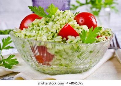 Salad with rice, tomato and green sauce. Selective focus.