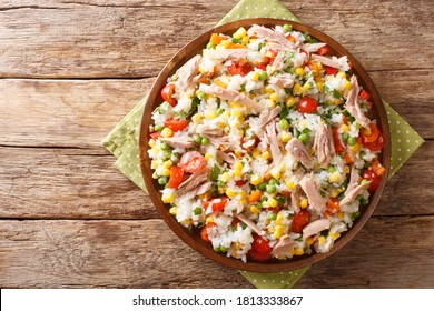 Salad of rice, tuna, tomatoes, sweet pepper, corn, green peas and herbs close-up in a plate on the table. horizontal top view from above