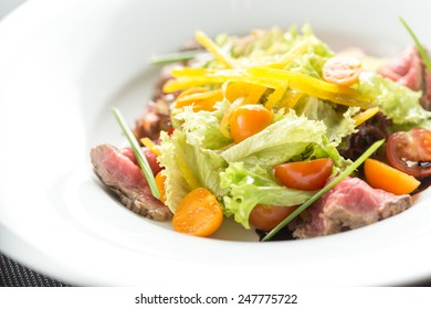 Salad with roast beef and vegetables isolated on black table