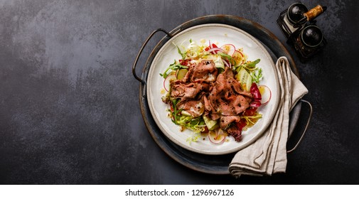 Salad with Roast Beef and vegetables on dark background copy space
