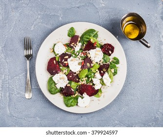 Salad with roasted beetroot, spinach, soft goat cheese and seeds in light plate over grey concrete textured background, oil in saucer. Top view