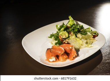 Salad with salmon on white plate