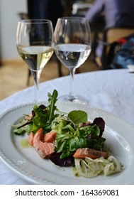 The salad with salmon is situated on the white plate. The salad contains: salmon, rocket (arugula), leaf lettuce, basil (or sweet basil)... and olive oil.