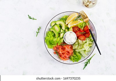 Salad of salted fish salmon, avocado, cherry tomatoes, cucumber, lettuce and cream cheese. Fish menu. Dietary menu. Seafood - salmon. Top view, overhead, flat lay