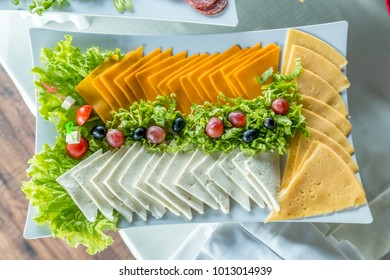 Salad with sausage, greens and other on table with white table. Catering concept.