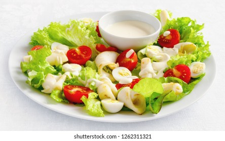 salad with seafood, lettuce, tomatoes, and quile eggs dressed with mayonnaise based sauce