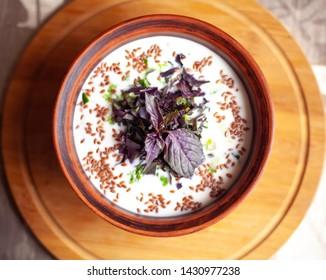 Salad seasoned with kefir. Tomato, cucumber, greens, kefir, flaxseeds. Proper nutrition.