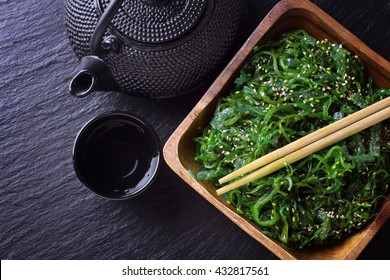 Salad with seaweed wakame, teapot and cup on black slade