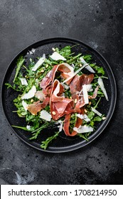 Salad with Serrano jamon, ham, rucola and Parmesan cheese. Black background, top view.