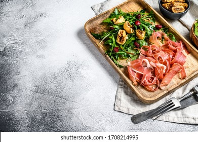 Salad with Serrano jamon, ham, rucola and fig. Antipasto. Gray background, top view, space for text