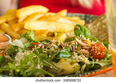 Salad with sesame, vinaigrette sauce, lettuca and fries on a plate served in a restaurant. Freshly slow cooked dish.